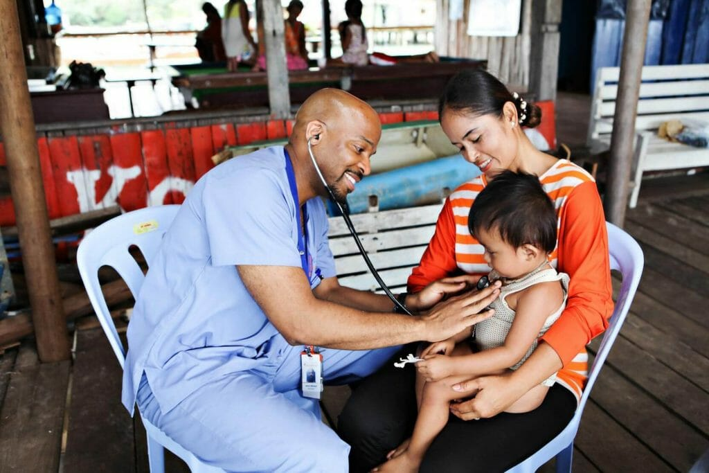 Photo of one of IMR's volunteer doctors checks the heartbeat of a child as he sits on his mother's lap