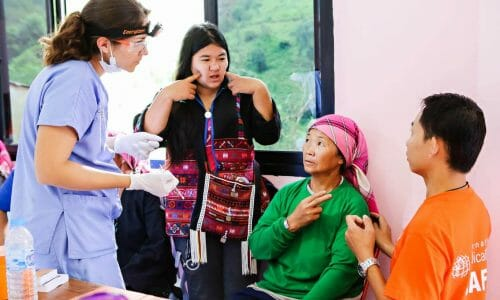 Photo of a volunteer interpreter asking questions of a patient to interpret for a doctor.