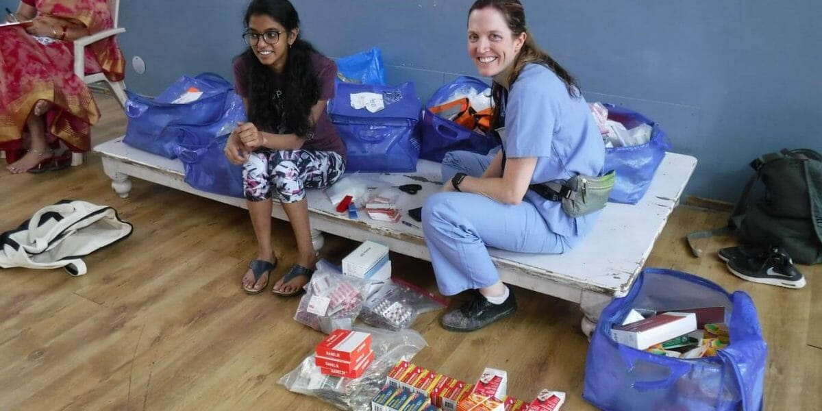 Photo of a female IMR volunteer with a patient | Short-term medical mission missions for graduate students from IMR offer the opportunity to participate in patient care in a clinic setting.