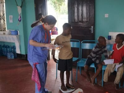 non-medical volunteer weighing a patient, Tanzania 2014