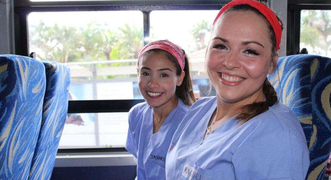 Two IMR volunteers traveling to clinic on a bus in Zambia | Short-term medical mission missions for undergraduate students from IMR offer the opportunity to participate in patient care in a clinic setting